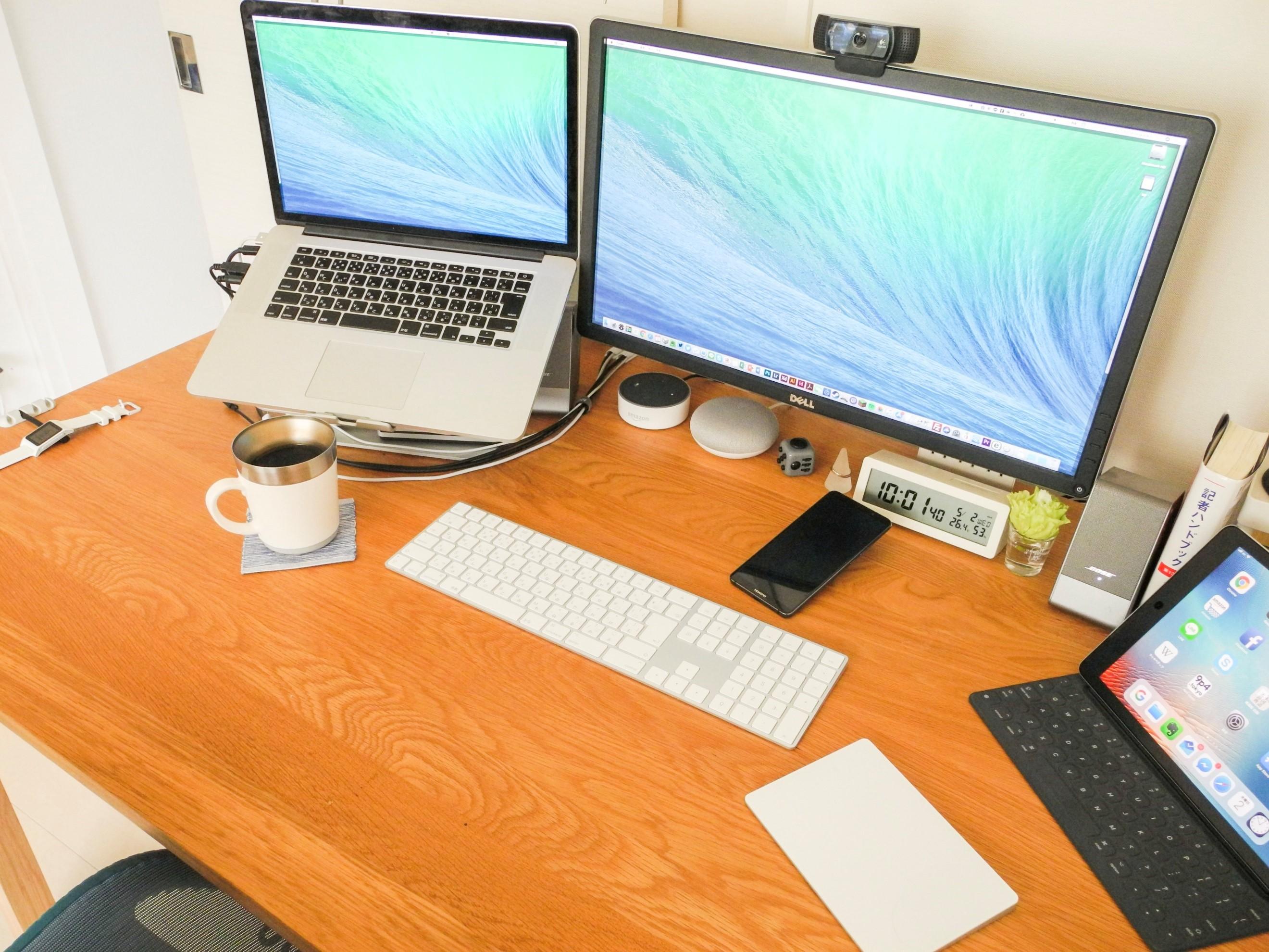 パソコンとコーヒーなどが置かれたデスクの様子