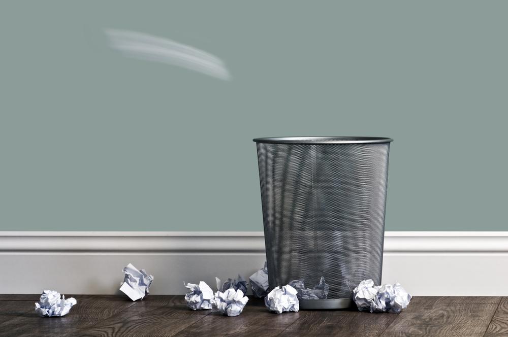 ゴミ箱に紙くずを捨てている様子
