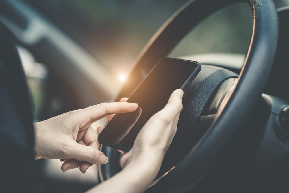 運転席でスマートフォンを操作する男性の手