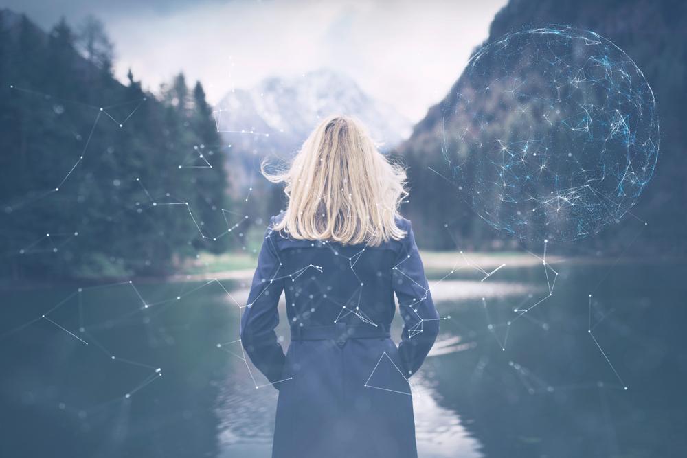 湖の前に立つ女性の後ろ姿