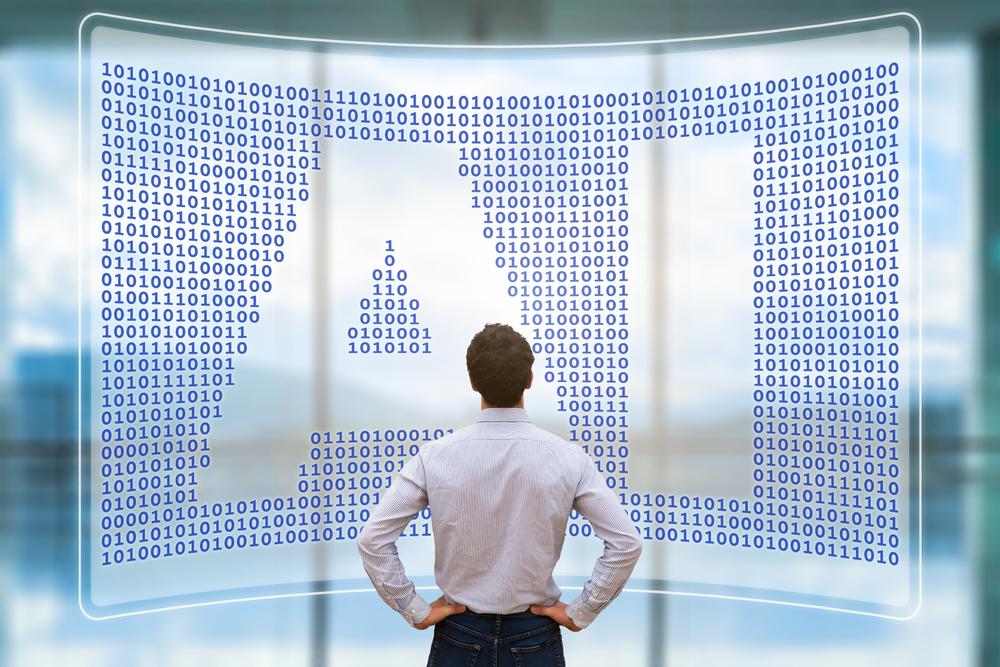 モニターに映る「AI」の文字を眺める男性の後ろ姿