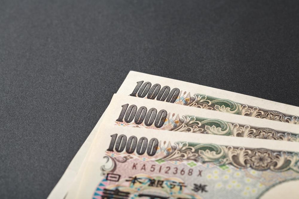 デスクの上に置かれた3枚の一万円札