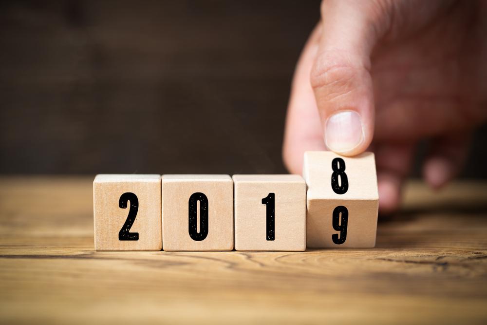 「2018」と書かれたブロックを「2019」に変えようとしている男性の手元